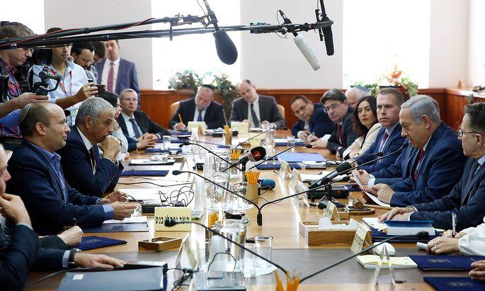 Ministerpräsident Benjamin Netanjahu (2. v. r.) einigte sich nach tagelangem Ringen nun doch mit Naftali Bennett (l.) von der Siedlerpartei.