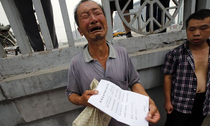 File picture shows a man crying as he shows his petitioning paper to Reuters journalists near the State Bureau for Petitions and Visits in Beijing
