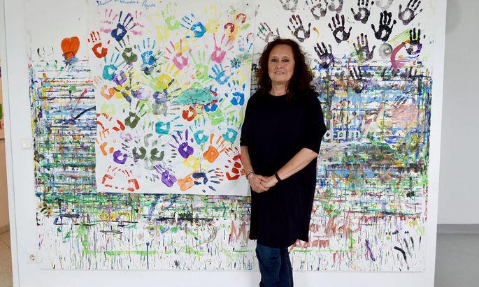 Andrea Brem vor einer von Kindern gestalteten Wand im Spielzimmer eines Wiener Frauenhauses – wo das genau ist, bleibt aus Sicherheitsgründen geheim.