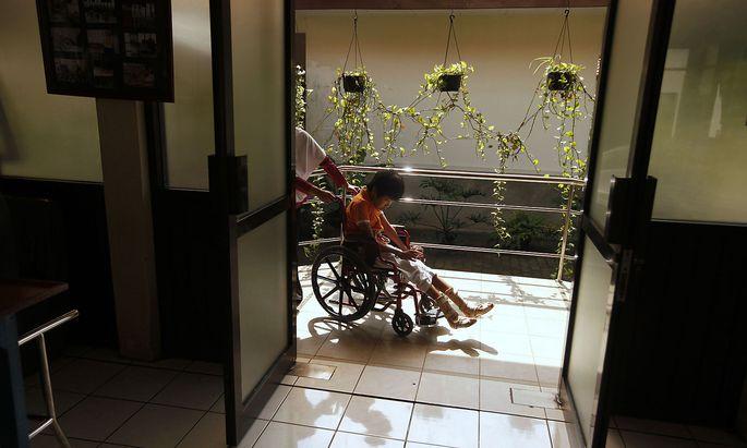 Ein Kind mit Zerebralparese wird im Rollstuhl geschoben. (Symbolbild)
