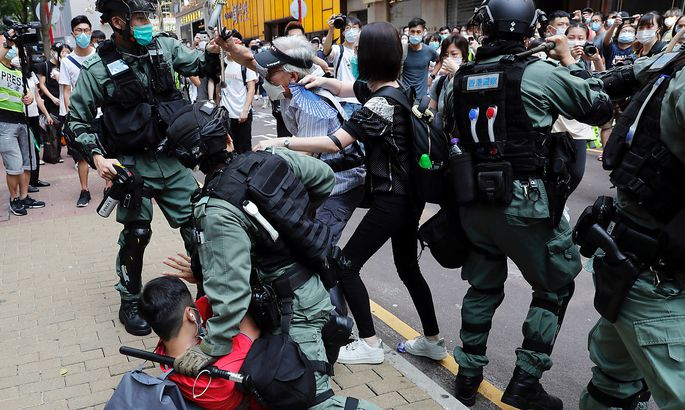 Anti-government demonstrators scuffle with riot police during a lunch time protest as a second reading of a controversial national anthem law takes place in Hong Kong