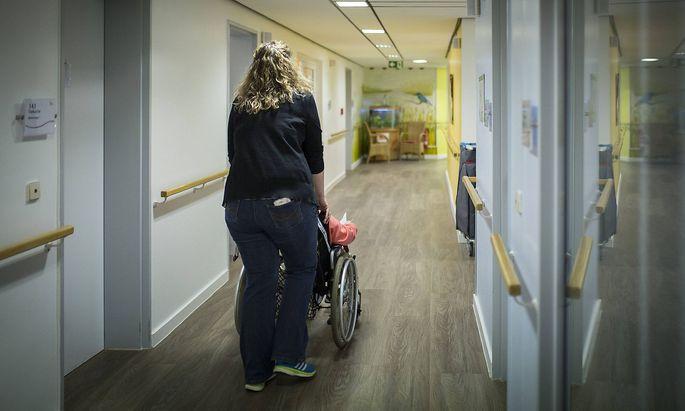 Eine Betreuerin schiebt eine aeltere Frau im Rollstuhl durch einen Gang in einer Pflegeeinrichtung