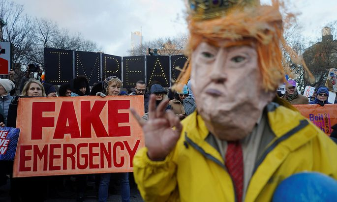 Protesters hold signs during a demonstration against U.S. President Donald Trump on Presidents' Day in Union Square, New York