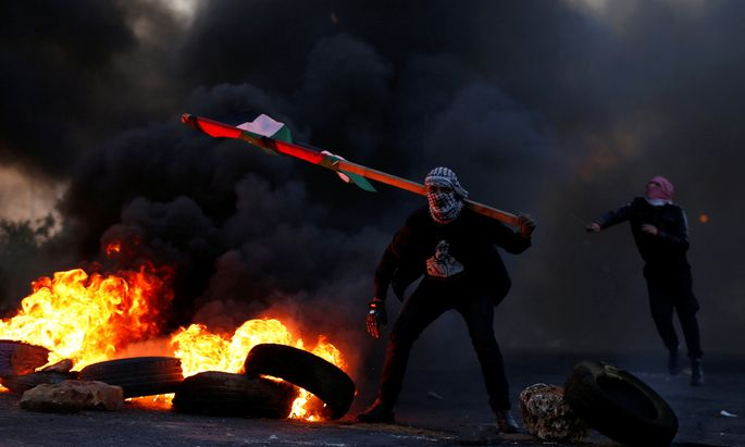Demonstrator holds a Palestinian flag during clashes with Israeli troops near the Jewish settlement of Beit El near Ramallah