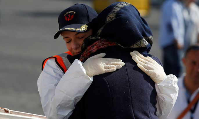 Regina Catrambone, co-founder of the Malta-based NGO Migrant Offshore Aid Station (MOAS), embraces a Syrian migrant as she disembarks from the MOAS ship Phoenix after it arrived with migrants and a corpse on board, in Catania on the island of Sicily