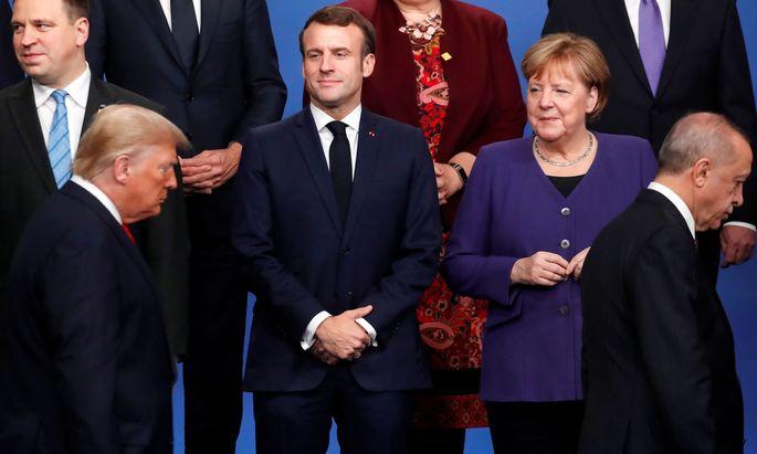 Vielsagende Blicke. Frankreichs Staatschef Macron und die deutsche Kanzlerin Merkel beobachten beim Nato-Gipfel die vorbeiziehenden Präsidenten Trump und Erdoğan.