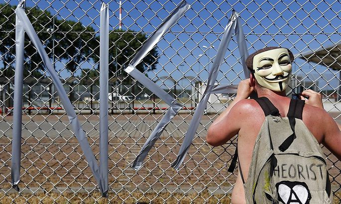 A protester tapes letters on a fence of the 'Dagger Complex' during a demonstration against the NSA in Griesheim