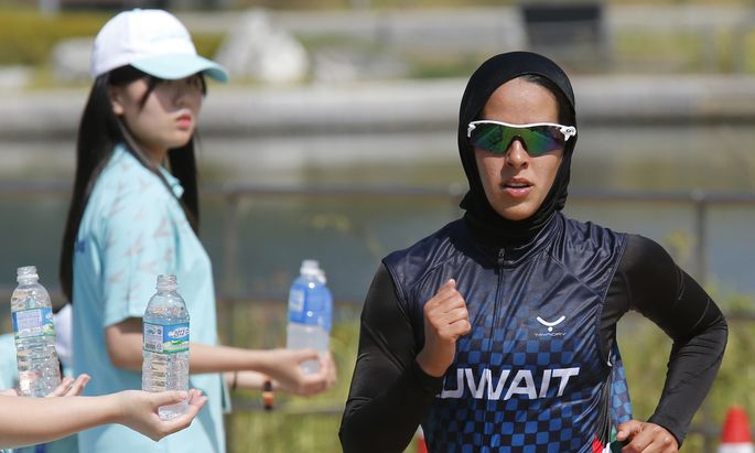 Kuwait´s I M Aljerewi, wearing a hijab, runs during the women´s triathlon competition at Songdo Central Park during the 17th Asian Games in Incheon