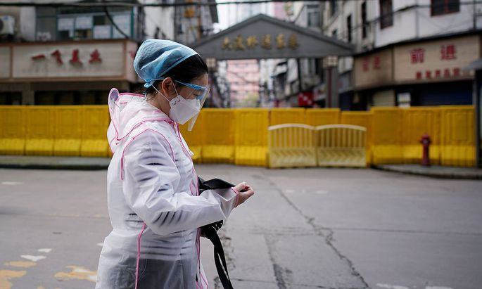 A woman wearing a face mask walks at a residential area blocked by barriers in Wuhan