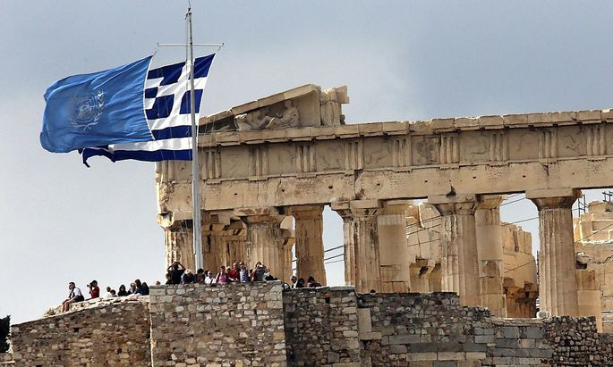 Greek and United Nations flags flutter atop the Athens Acropolis on United Nations Day in Athens