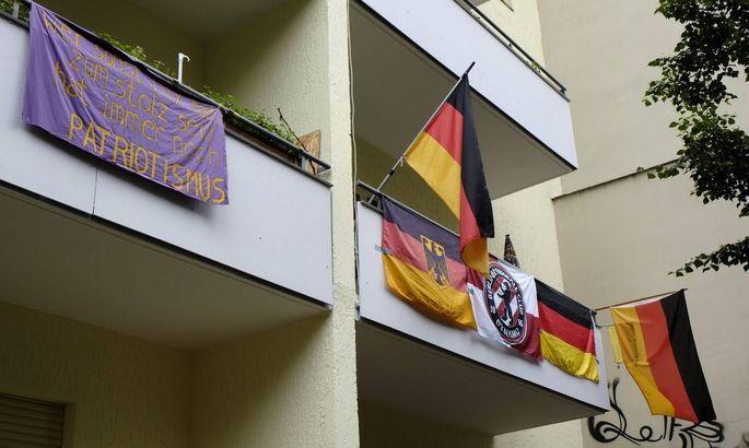 Deutschlandfahnen schmuecken ein Wohnhaus in der Schoenleinstrasse in Berlin Kreuzberg snapshot photog