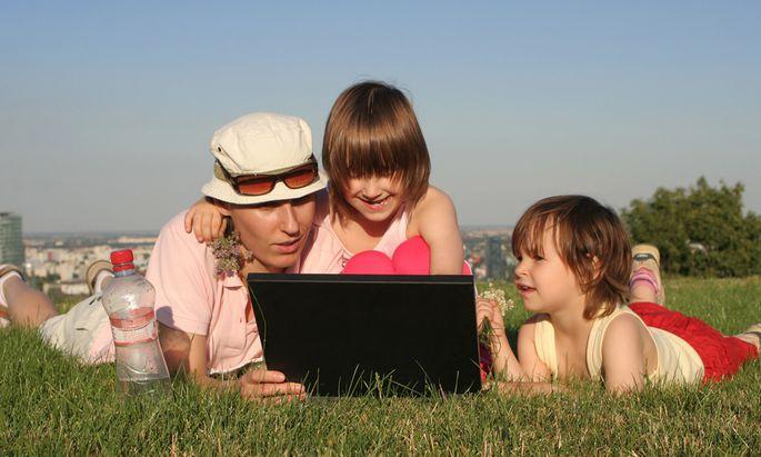 Frau und Kinder mit Notebook auf einer Wiese