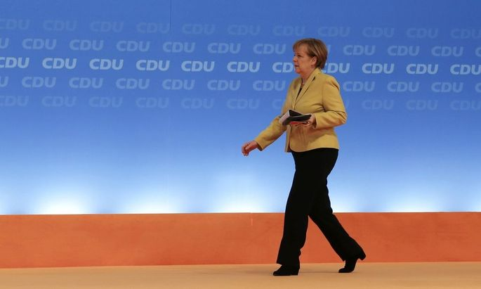 German Chancellor and CDU leader Merkel walks on stage during the party convention in Cologne