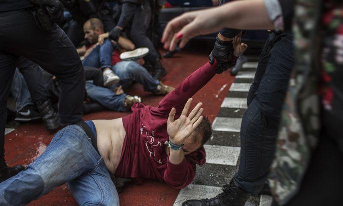 Polizisten zerren in Barcelona einen Demonstranten weg, der ein Abstimmungslokal schützen wollte.