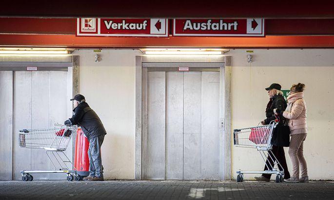Menschen stehen mit Einkaufswagen vor einem Supermarkt und warten auf den Einlass, aufgenommen in Goerlitz, 02.04.2020.
