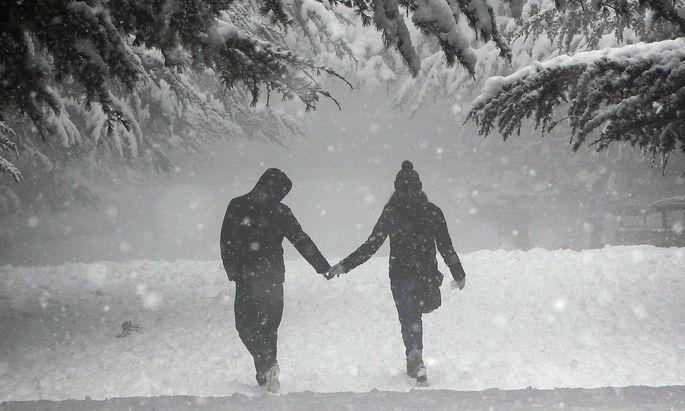 A couple walk during a snowfall in an amusement park in Tbilisi