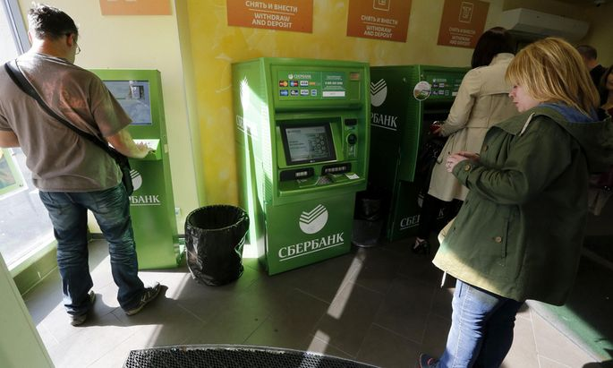 People use an automated teller machine inside a branch of Sberbank in St. Petersburg