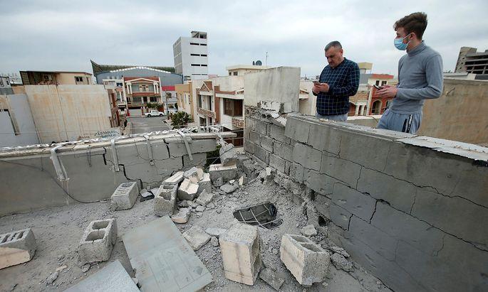 Schadensbesichtigung auf einem Hausdach nach dem Raketenangriff in Erbil.