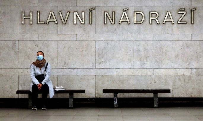 FILE PHOTO: A commuter wearing a protective mask waits for a subway train in Prague