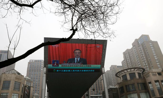 A giant screen shows Chinese Premier Li Keqiang delivering a speech during the opening session of the National People´s Congress (NPC) at the Great Hall of the People, in Beijing