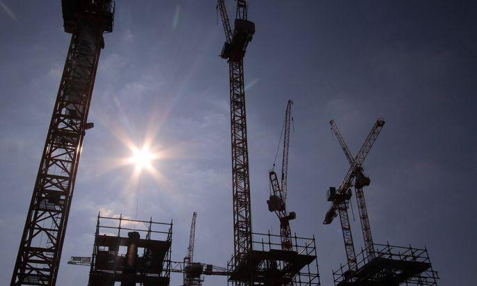 Symbolbild Bauwirtschaft: Silhouetten von Baukraenen und Baugeruesten in der heiszen Nachmittagssonne in Frankfurt, Hessen