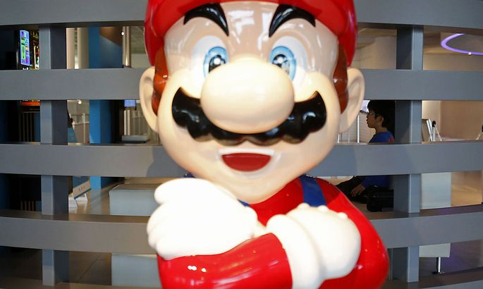 A boy seated behind a Super Mario figure watches a monitor displaying Nintendo Co Ltd´s Wii U game console at its showroom in Tokyo