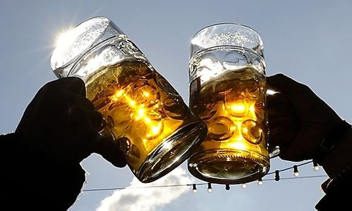 Visitors toast each other on a sunny day during Oktoberfest in Munich