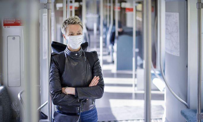 Eine Frau steht in einer S-Bahn der Berliner Verkehrsbetriebe. Sie traegt einen Mundschutz. Berlin, 13.04.2020. Aktuell