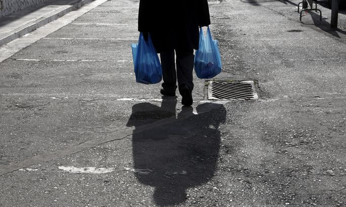 A man carries bags which were distributed to him during a donation program of the municipality of Athens