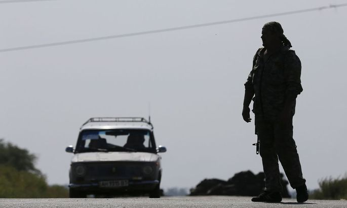 A car moves towards the direction of a pro-Russian separatist at a checkpoint outside the village of Kreminets near the city of Donetsk