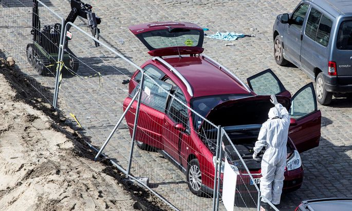 A forensics expert stands next to a car which had entered the main pedestrian shopping street in the city at high speed, in Antwerp