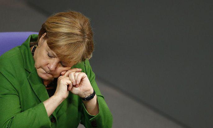 German Chancellor Merkel listens to a debate about NSA surveillance during Bundestag session in Berlin