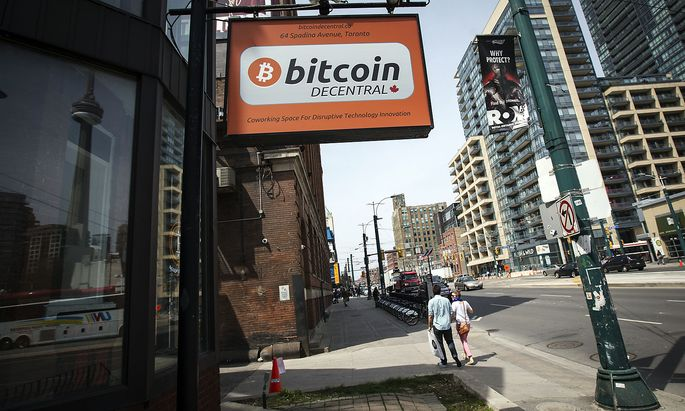 People walk by a 'Bitcoin Decentral' sign in Toronto