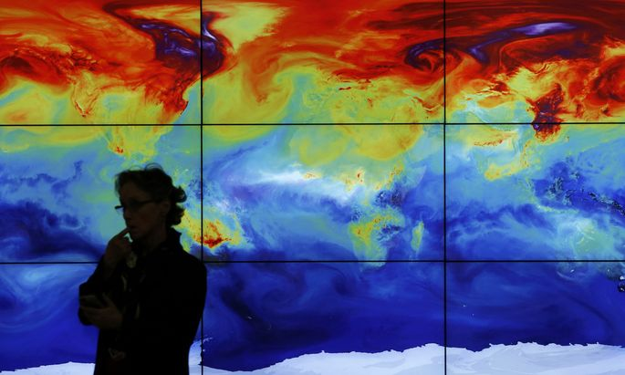A participant is pictured in front of a screen projecting a world map during the World Climate Change Conference 2015 (COP21) at Le Bourget