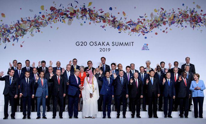 Gruppenfoto mit zwei Alphatieren. Fast alle winken und lächeln, US-Präsident Trump und der saudiarabische Kronprinz, Mohammed bin Salman, schütteln Hände.
