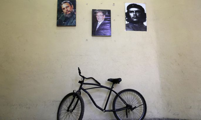 A bicycle is parked under pictures of Cuba´s former president Fidel Castro, Raul Castro, brother of Fidel and Cuba´s president, and revolutionary hero Ernesto ´Che´ Guevara in an office in Havana