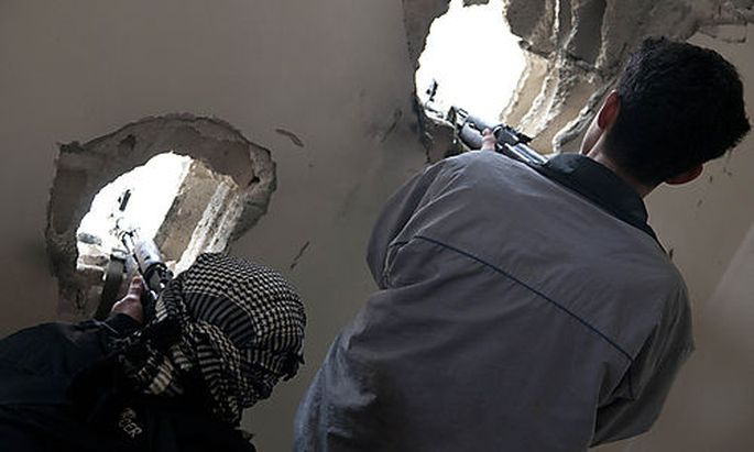 In this photo taken on Monday Dec. 19, 2011, defected Syrian soldiers position their rifles as they t