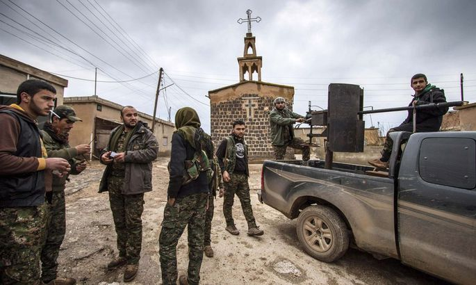 Fighters of the YPG stand near a pick-up truck mounted with an anti-aircraft weapon in front of a church in the Assyrian village of Tel Jumaa