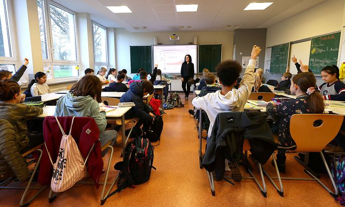 Students raise their hands during a lesson with geography teacher Dinar Pamukci at Hesse's largest high school, Karl-Rehbein-Schule