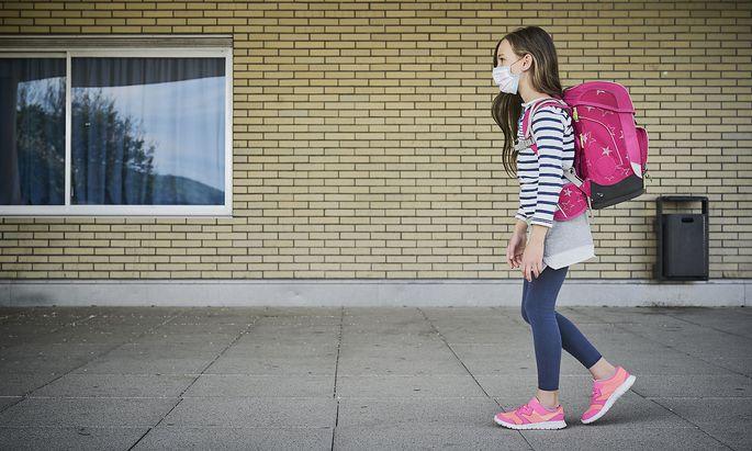 Girl wearing mask and schoolbag walking along building