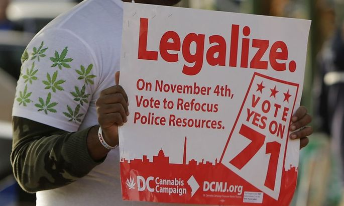 Melvin Clay of the DC Cannabis Campaign holds a sign urging voters to legalize marijuana, in Washington