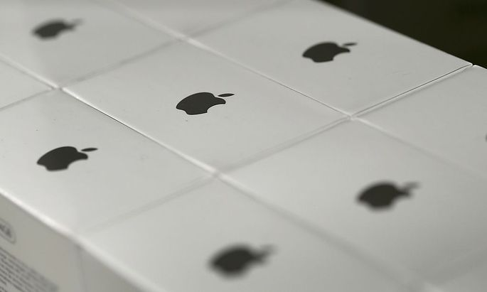 Apple logos are seen on boxes in a shop in Munich