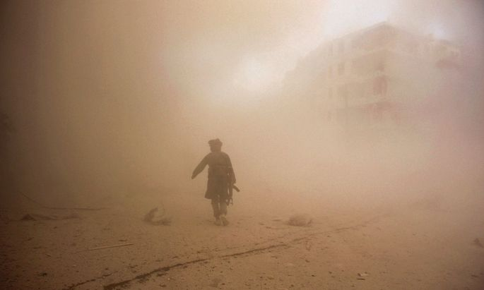 A rebel fighter runs through dust towards an area damaged by what activists said were barrel bombs dropped by warplanes loyal to Syria´s President Assad in Aleppo