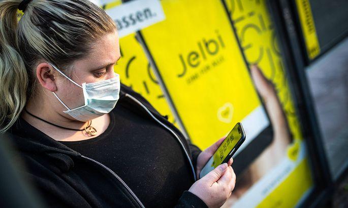 Ein Frau mit einer Mund-Nasen-Maske nutzt die BVG -App auf ihrem Smartphone an einer Bushaltestelle der BVG in Berlin.