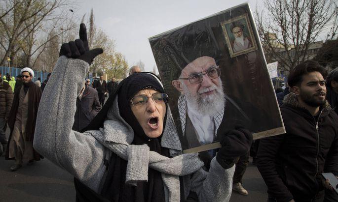 Proteste gegen die USA - Demonstrantin hält ein Plakat mit dem Konterfei von Khamenei