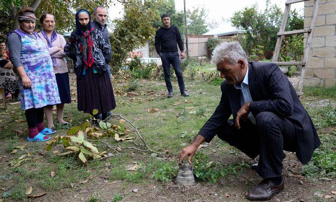 Bewohner der Stadt Beylagan in Aserbaidschan betrachten Reste eines mutmaßlich armenischen Geschosses.