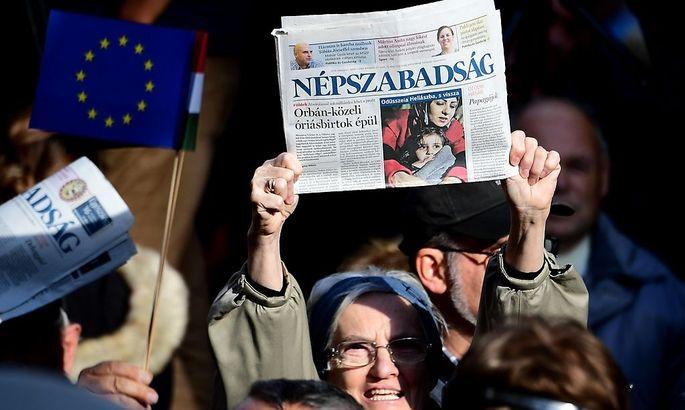 """Demonstranten mit einer Ausgabe der """"Nepszabadsag""""."""