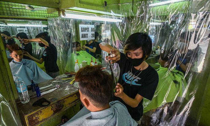 Auf den Philippinen haben Friseure Plastikvorhänge montiert, um der Virenverbreitung vorzubeugen.