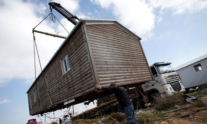 Ein Mann hilft ein Haus in Amona zu entfernen.