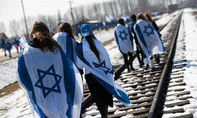 People wear Israeli flags around their shoulders as they walk on the railroad tracks inside the former Nazi death camp of Birkenau